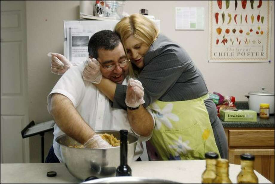 Stephanie Lane hugs Capital Clubhouse member Joey Scardina while they prepare lunch Monday. The program in Olympia helps those with mental health issues. Photo: Dan DeLong/Seattle Post-Intelligencer