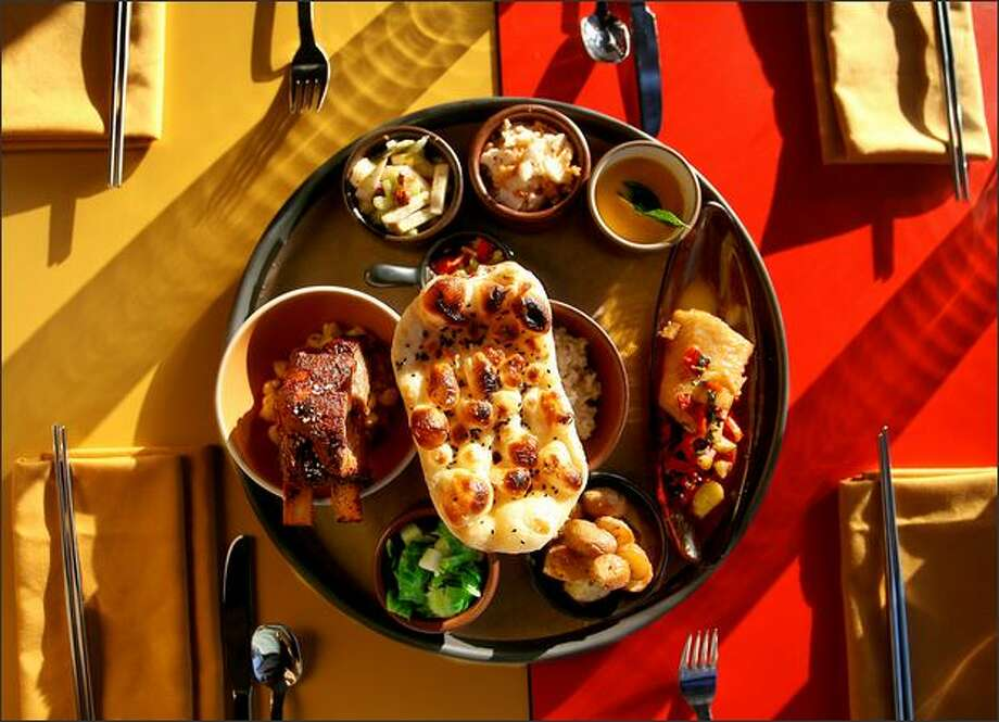 In this thali, from left counter clockwise: Berkshire pork short ribs on smashed chickpeas, brussels sprouts with apple and Szechuan peppercorn, fingerling potatoes with five seeds, black cod with sunchoke, peppers, mint and orange, pumpkin curry-leaf soup, shaved cauliflower salad, Asian pear, celery and hazelnut salad, green tomato chutney (partially obscured by nigella naan, which covers a bowl of matsutake haiga rice). Photo: Scott Eklund/Seattle Post-Intelligencer