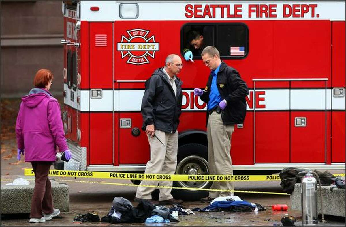 Investigators and medics investigate the scene and attend to a 61-year-old man in the ambulance after he set himself on fire in crowded Red Square at the University of Washington on Thursday. The act stunned hundreds of students that witnessed the event as classes were letting out.