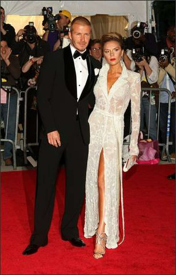 """Soccer star David Beckham and wife Victoria arrive at the Metropolitan Museum of Art Costume Institute gala for Thursday's opening of the exhibit """"Superheroes: Fashion and Fantasy,"""" in New York. The annual gala has become a red-carpet showcase for designer gowns worn by celebrities. It has become New York's top red-carpet event of the year. Photo: Getty Images"""