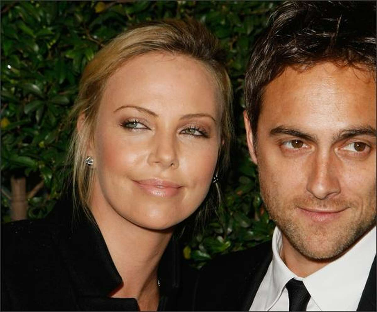 Actress Charlize Theron (L) poses with actor and director Stuart Townsend on arriving at the screening of