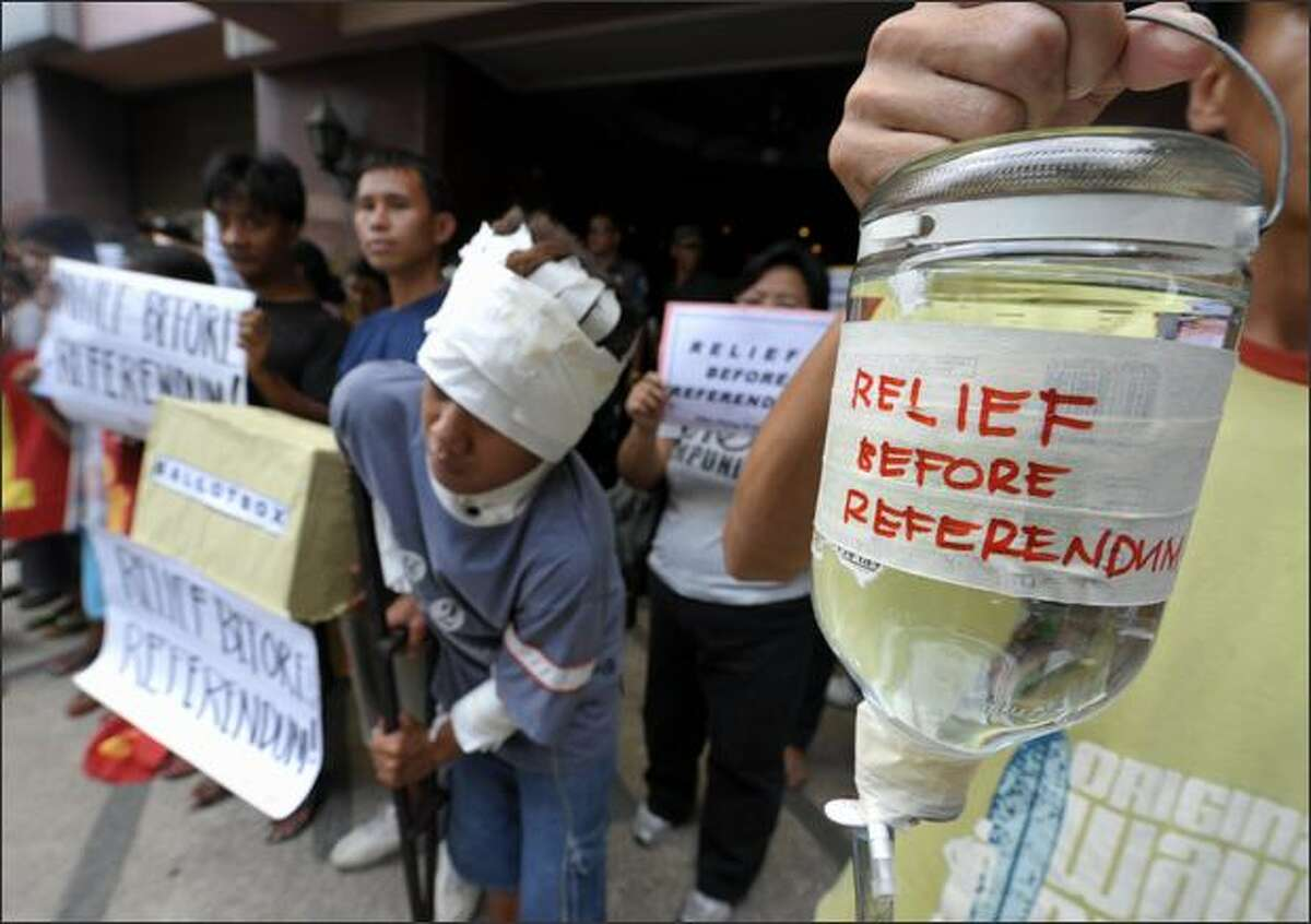 Protesters demonstrate outside the Myanmar embassy in Manila to urge the ruling junta to allow outside help for survivors of Cyclone Nagris. The cyclone slammed in the southern coast of Myanmar on May 3, 2008, leaving at least 22,000 people dead and another 41,000 missing by the official count, with the toll widely expected to rise. AFP PHOTO/Jay DIRECTO