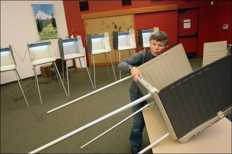 "Election volunteer Pat Burton sets up privacy voting booths at East Shore Unitarian Church in Bellevue on Monday. ""I have mixed emotions about it,"" Burton said about this election being the last time most voters can actually go to the polls. Burton has been an election volunteer for five years. Photo: Mike Kane/Seattle Post-Intelligencer"