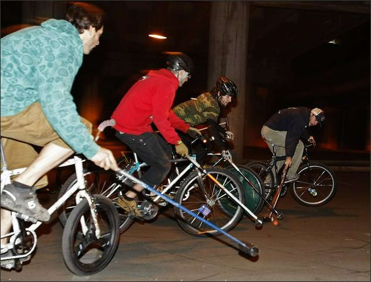 Riders fight for the ball with homemade mallets underneath Interstate 5 at Northeast 65th Street. Matches usually are played here on Thursday evenings around 7.