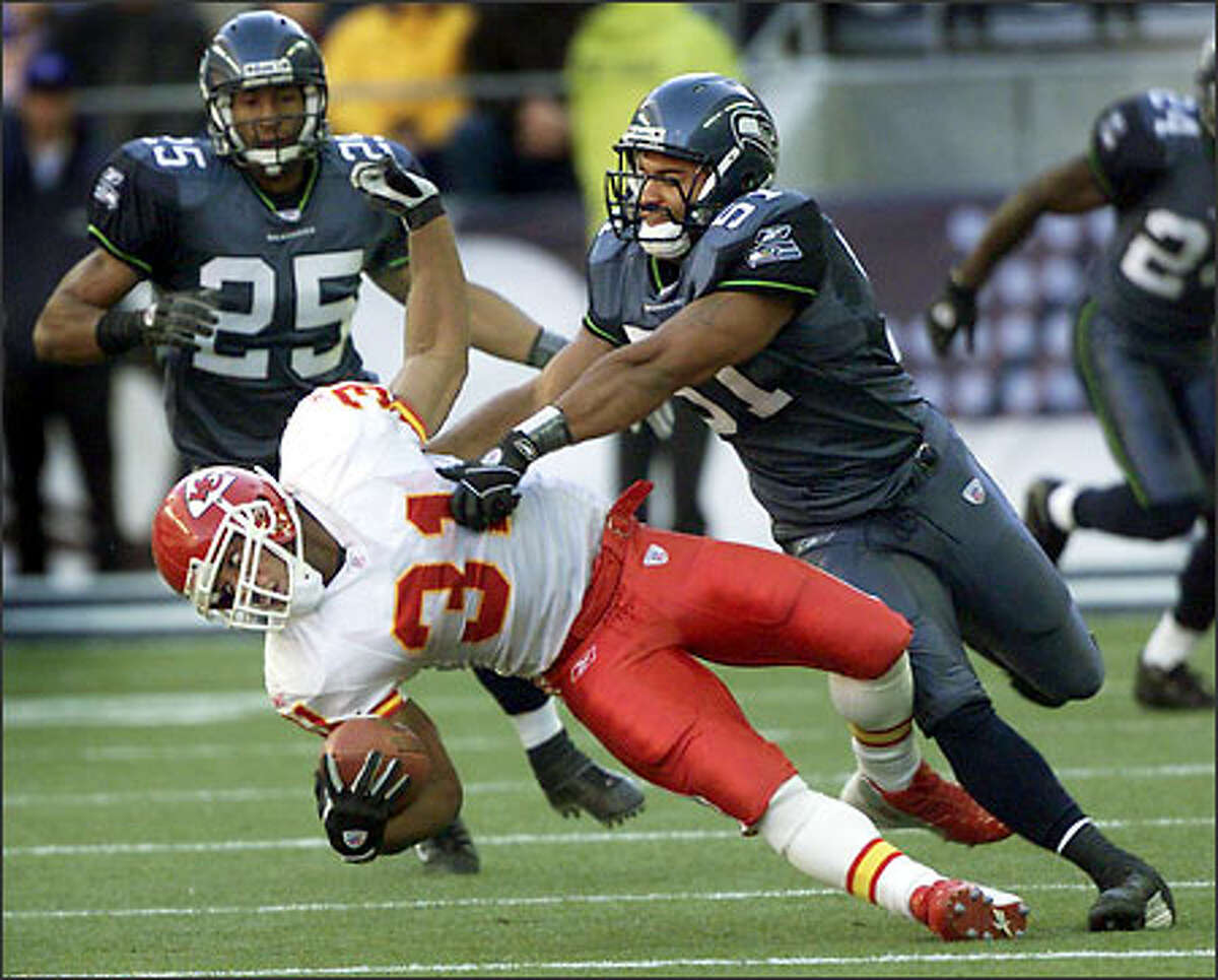Anthony Simmons, after missing eight games, knocks Chiefs running back Priest Holmes to the ground for one of the Seahawks linebacker's six tackles.
