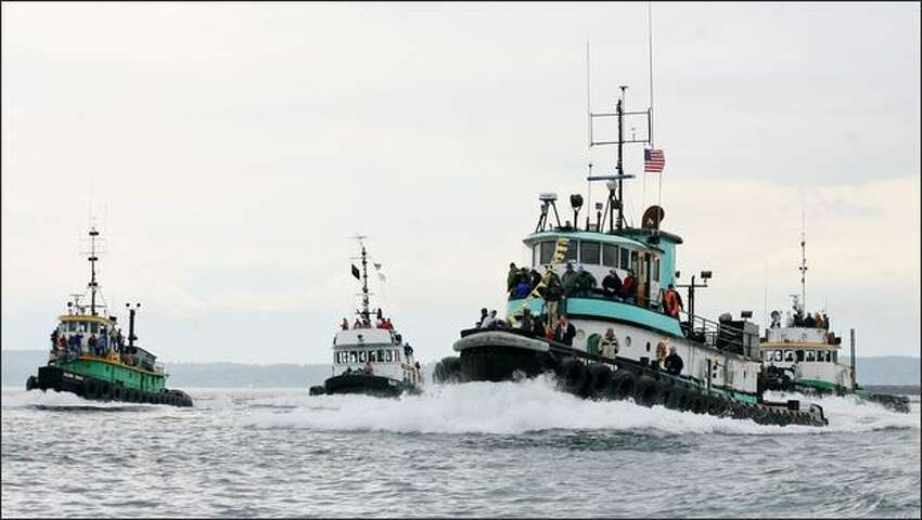 The Island Star (Island Tug & Barge) leads the field of 10 boats during the Class B Harbor Tug Race on Elliott Bay. Island Star won with a time of 6 minutes and 53 seconds.