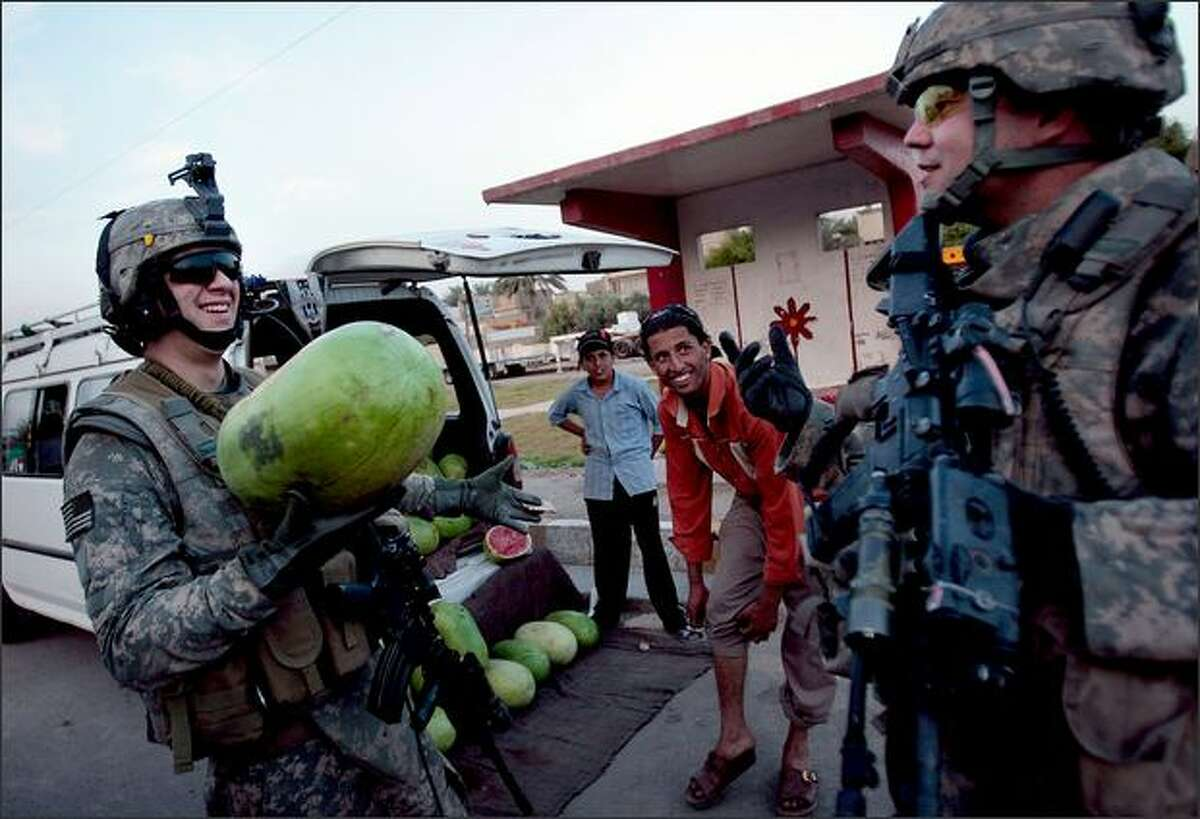 Cpl. Daniel Hirsch of Liberty, New York, left, asks Staff Sgt. Robert Thomas of New Burgh, Indiana, right, what to do with the watermelon he had just bought from a bemused street vendor in east Baghdad, Iraq. Both soldiers are in the 3-89 Cavalry Regiment of the 10th Mountain Division.
