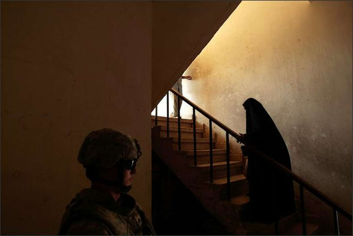 A U.S. soldier with the 3-89 Cavalry Regiment of the 10th Mountain Division stands guard for his visiting commander while a woman ascends stairs in a government services building in the Rusafa neighborhood of east Baghdad, Iraq.