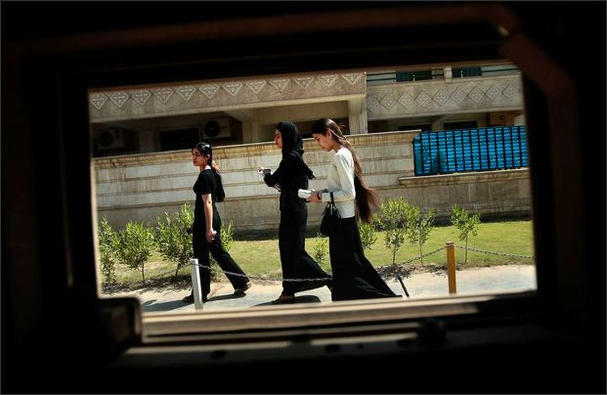 Young Iraqi women walk on the sidewalk outside a window in the Rusafa neighborhood of east Baghdad, Iraq. Rusafa has largely been spared the violence that has plagued other east Baghdad Shiite neighborhoods recently.
