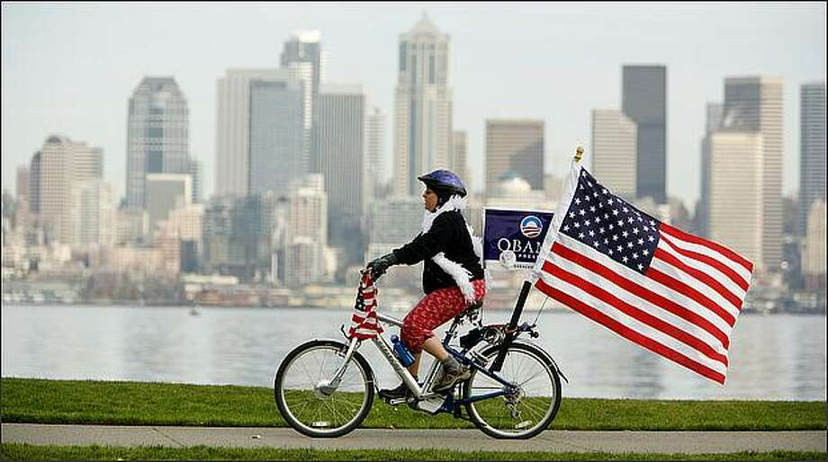 "Val Mallinson bikes along Harbor Avenue in West Seattle on Wednesday, celebrating Barack Obama's election. Mallinson also cruised up and down California Avenue in West Seattle on Election Day. ""I voted absentee and I just wanted to be part of it publicly,"" she said. Photo: Paul Joseph Brown/Seattle Post-Intelligencer"