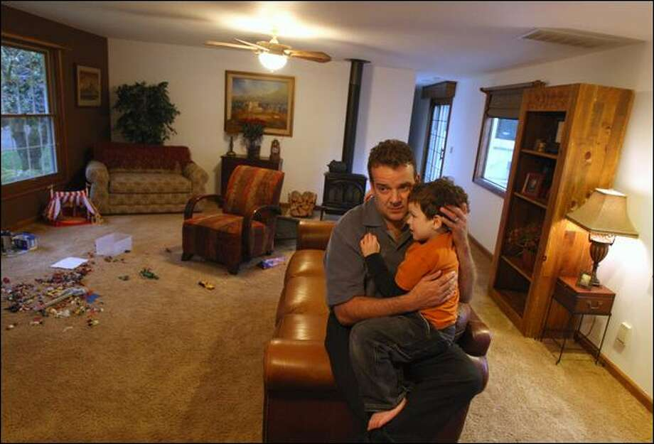 Real estate broker Robert Ott and his autistic son, Aaron, 6, find a quiet moment at their home in Renton. Because of the slump in home sales, Ott and his wife, Renee, are finding it difficult to maintain the expensive behavioral therapy that Aaron requires and which is particularly needed at this time in his life. Photo: Mike Kane/Seattle Post-intelligencer Photos