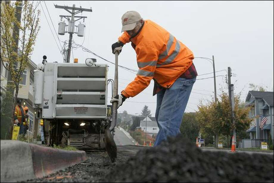 A worker removes old asphalt recently at a Tacoma Public Works project as many other paving projects are put on hold during a nationwide asphalt shortage. Photo: Ted S. Warren/Associated Press