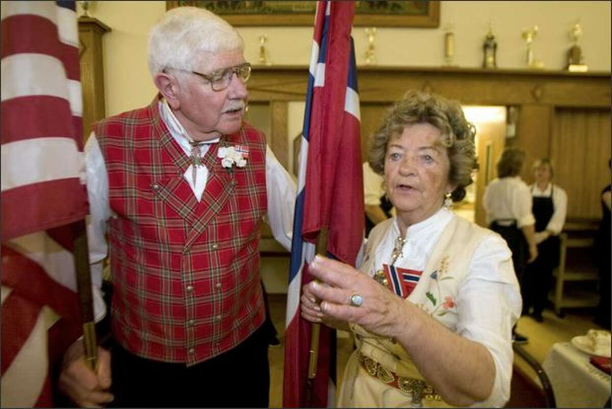 Flag bearers Ted Forsberg, left, and Unn Maeland discuss which way to go while attending the Norwegian Constitution Day luncheon at the Lief Erikson Hall in Ballard.