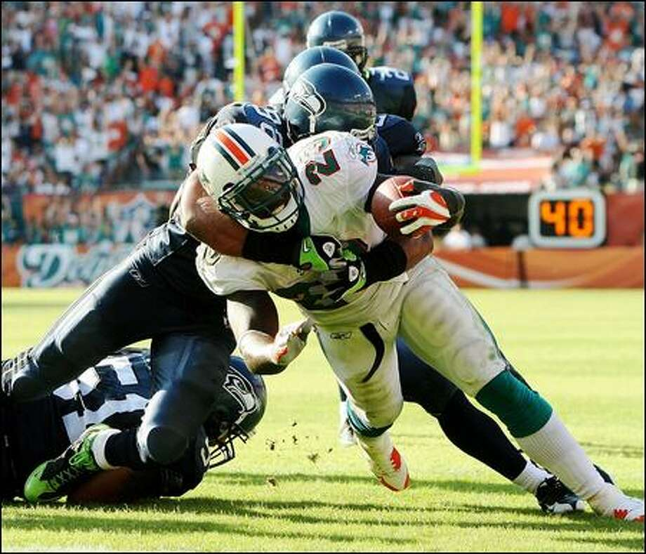 The Dolphins' Ronnie Brown finishes off a 16-yard touchdown run in the fourth quarter as the Seahawks' Julian Peterson tackles him at the goal line. Photo: Doug Benc/Getty Images