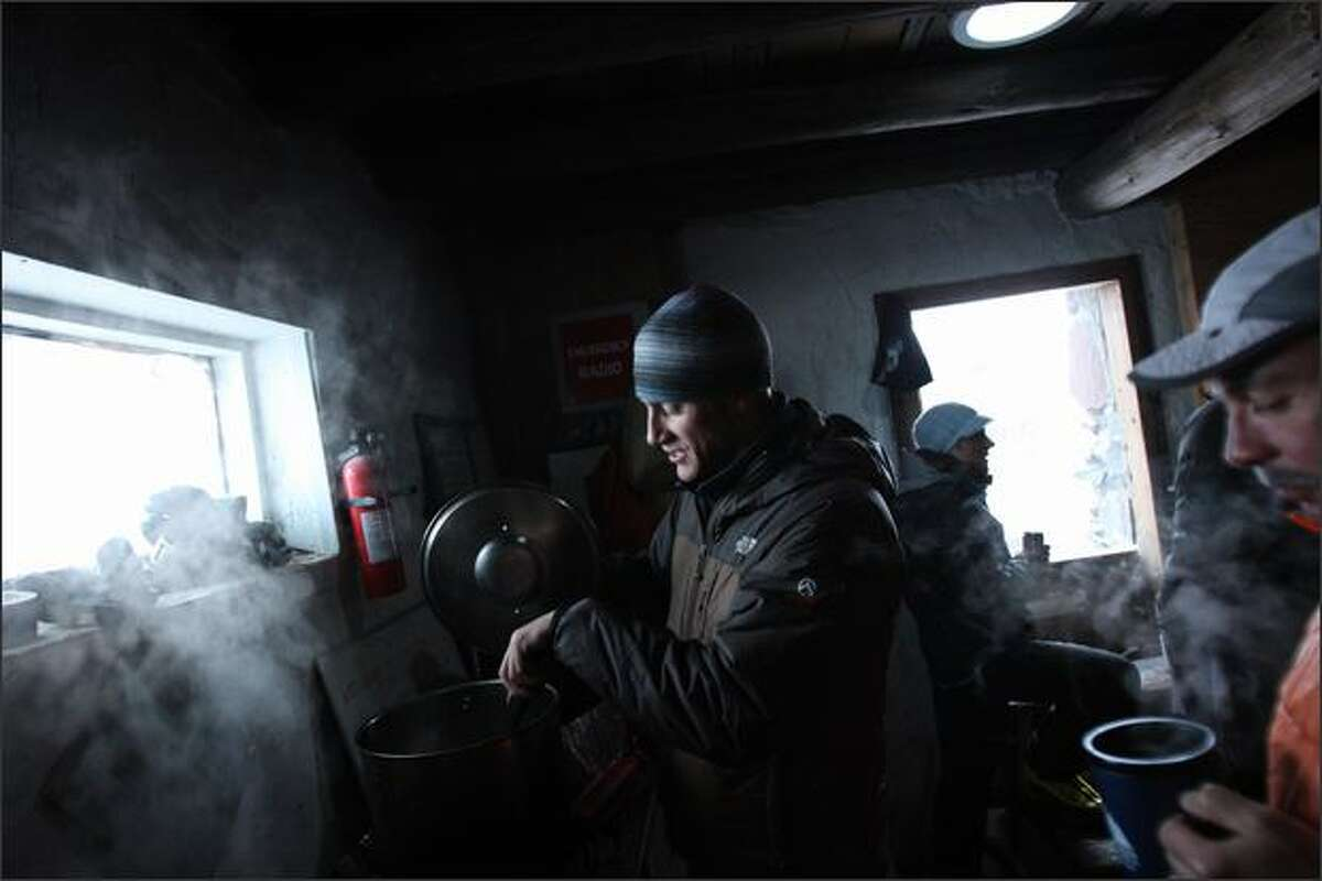 Professional mountaineer Matt Farmer, left, based in Seattle, boils water while chatting with Julian Simon, a researcher with Fred Hutchinson, in the public shelter at Camp Muir at about 10,000 feet, on Mt. Rainier.