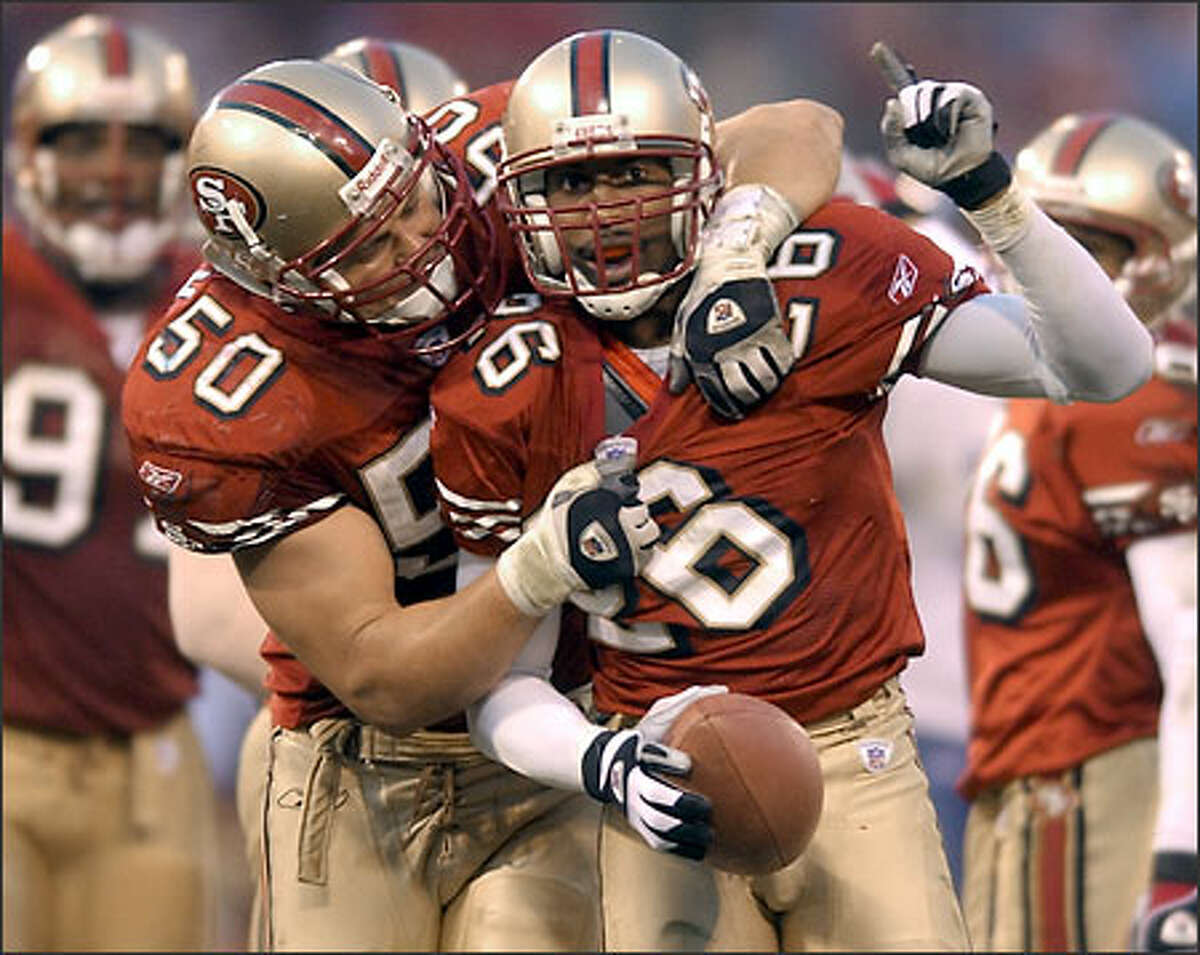49ers linebacker Derek Smith grabs cornerback Rashad Holman after his interception of a Matt Hasselbeck pass ended the Seahawks' final drive.
