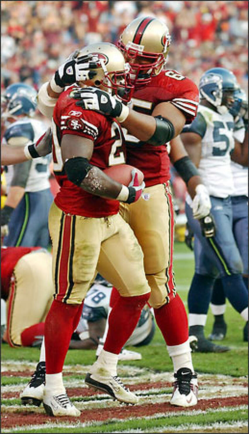 49ers running back Garrison Hearst is congratulated by guard Ron Stone after scoring in the fourth quarter, the third of his career-high three touchdowns.