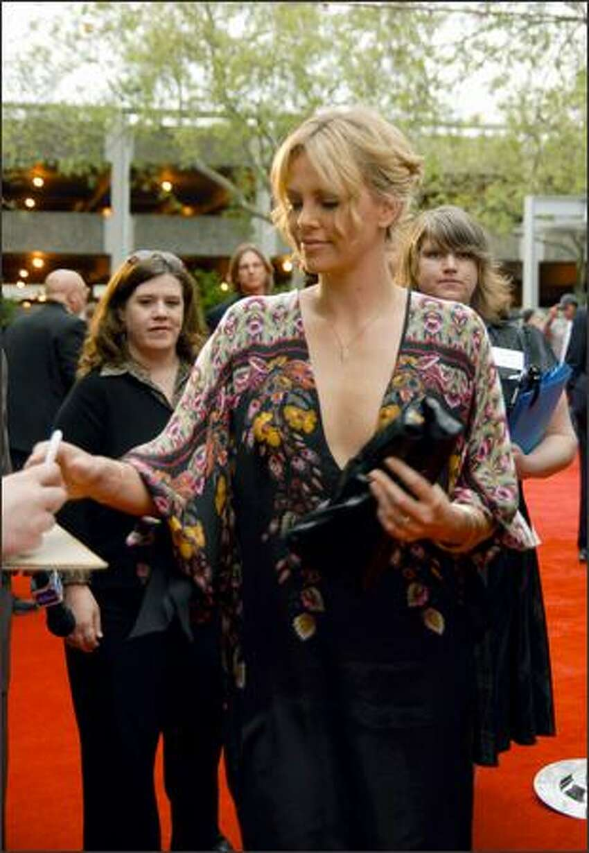 Charlize Theron signs an autograph for a fan on the red carpet at the Seattle International Film Festival on Thursday evening.