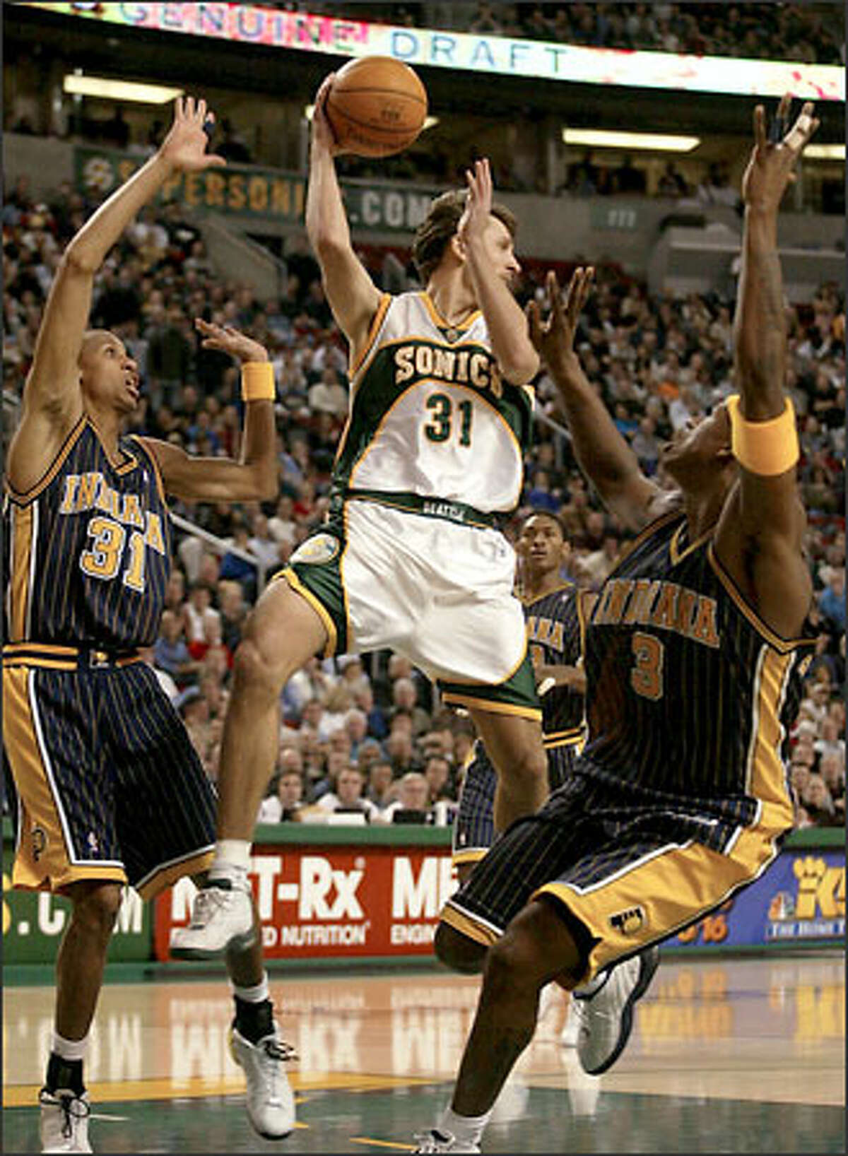 Sonics' Brent Barry passes over Al Harrington, right, and Reggie Miller.