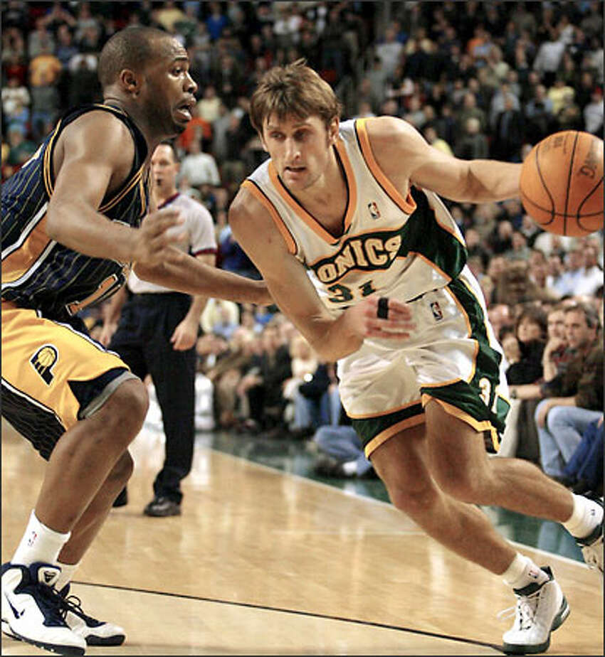 Sonics' Brent Barry dribbles past Pacers' Jamaal Tinsley.