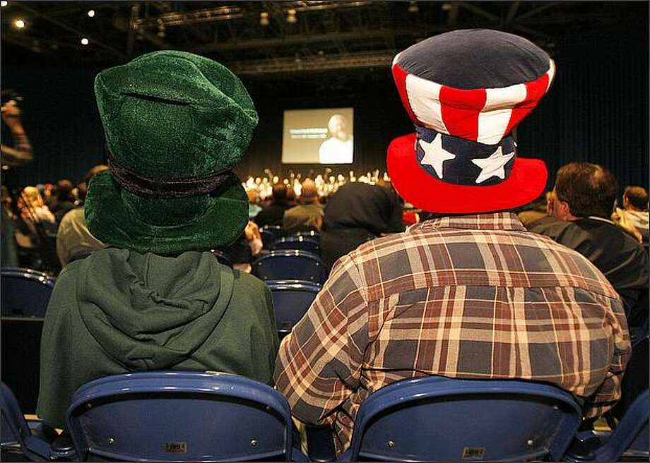 Nic McLean and his father, Jim, of Redmond, were among many who wore funny hats in honor of Edward McMichael during a memorial service held at the Qwest Field Events Center in Seattle. Photo: Mike Urban/Seattle Post-Intelligencer
