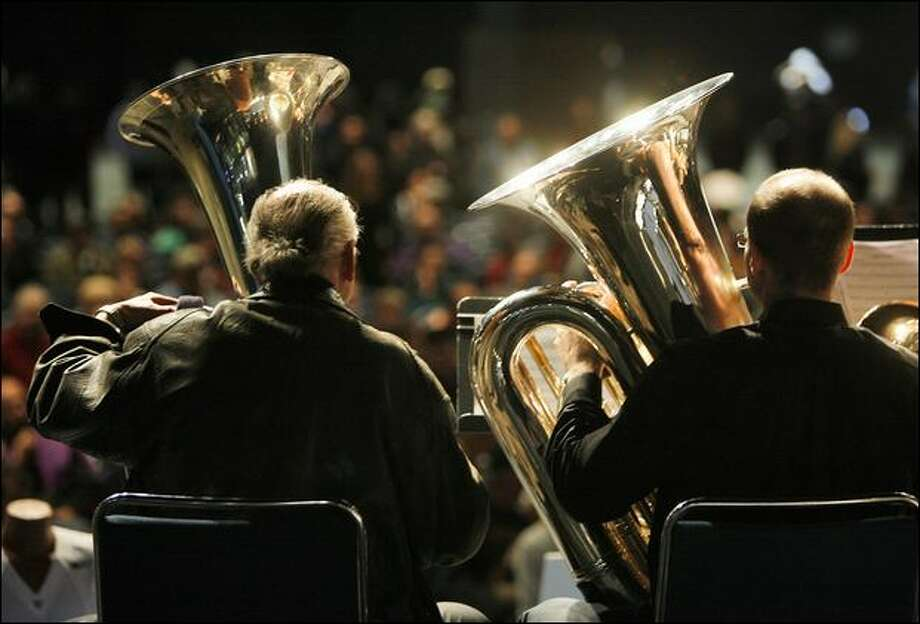 Seattle Symphony Orchestra's principal tuba player Chris Olka, left, and retired principal player Michael Russell perform during a memorial service for Tuba Man. Photo: Mike Urban/Seattle Post-Intelligencer