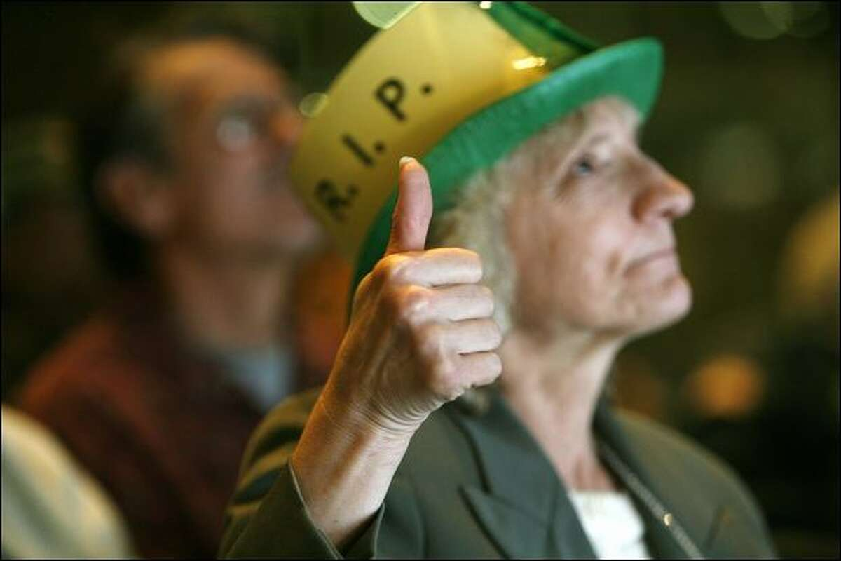 Louise Hohbach, of Seattle, gives a tributary thumbs-up for slain Edward McMichael, aka Tuba Man, during a memorial service Wednesday.