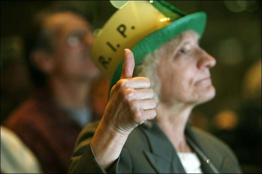 Louise Hohbach, of Seattle, gives a tributary thumbs-up for slain Edward McMichael, aka Tuba Man, during a memorial service Wednesday. Photo: Mike Urban/Seattle Post-Intelligencer