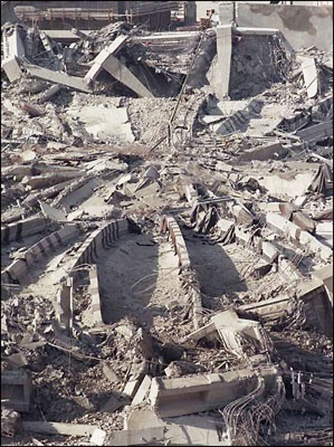 Not everything was leveled by the blast. The flagpole from the top of the Kingdome remained standing amid the rubble. You can see it toward the top of this photo, leaning to the right. Photo: Grant M. Haller, Seattle Post-Intelligencer