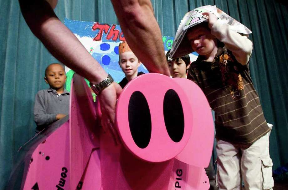 "A group of second graders are the first to roll the new ""RolyPig"" composter during an assembly at Springdale School in Stamford, Conn. on Thursday March 24, 2011.  The city of Stamford purchased sux composters to aid the districts second graders in their gardening curriculum. Photo: Kathleen O'Rourke / Stamford Advocate"