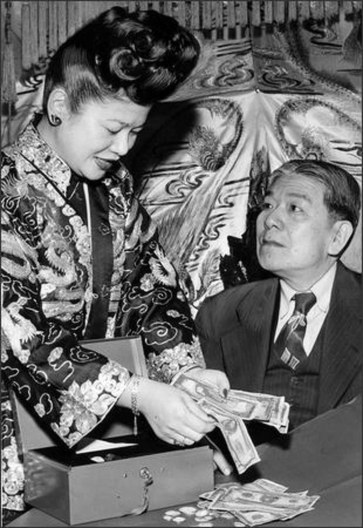 12/10/1949 - Ruby Chow owner of Ruby Chow's Restaurant and Jackman Chin, vice presidnt of the Chinese Benevolent Association, happily count out Chinatown's contribution to the Seattle Post-Intelligencer Christmas Fund.