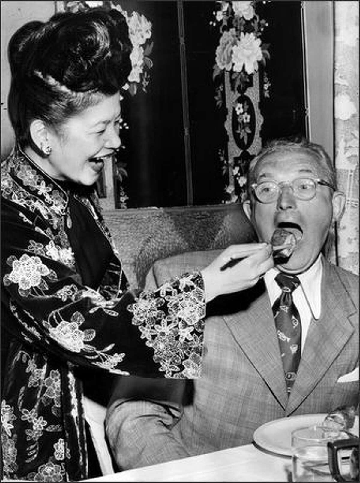 07/23/1951 - Ruby Chow feeding Tommy Dorsey egg roll via chop sticks