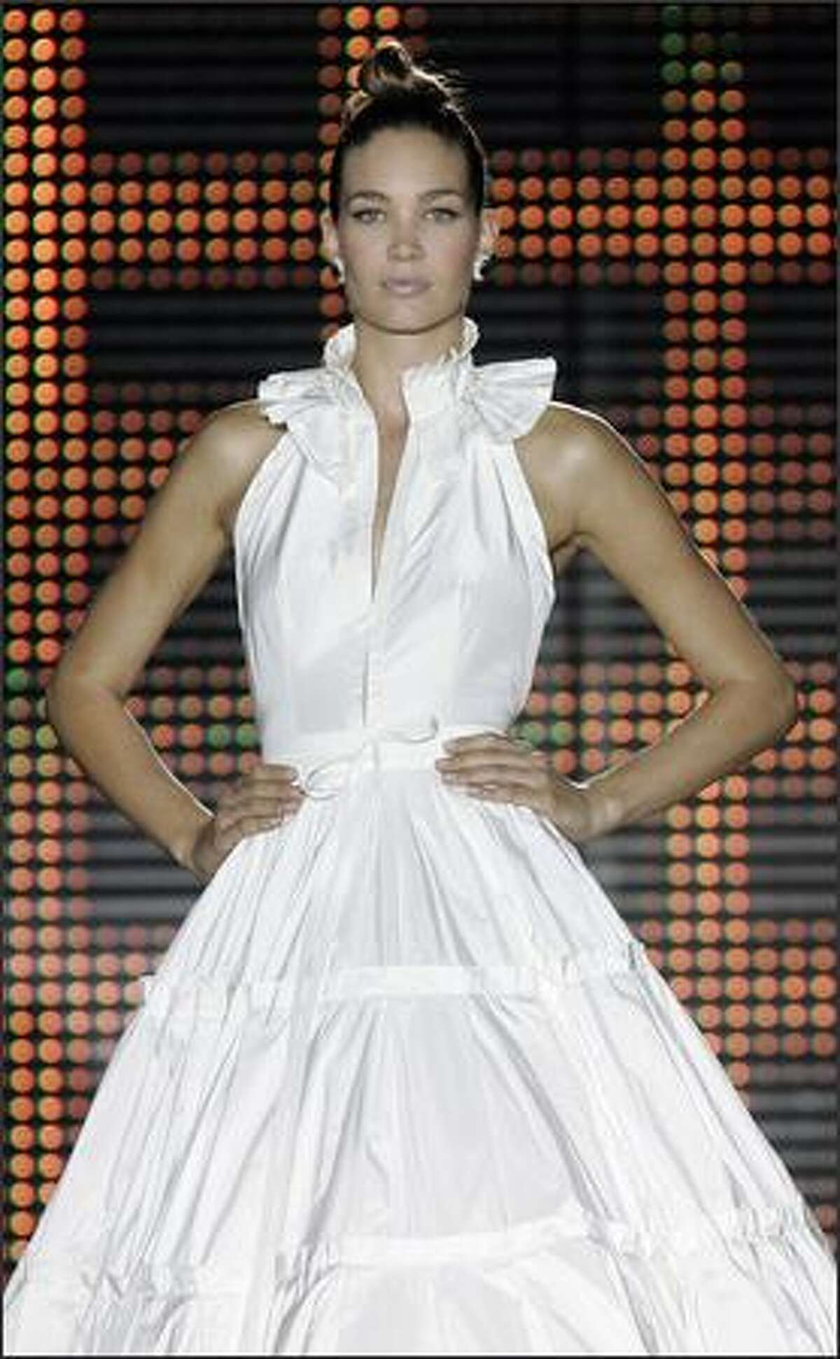 Models present wedding gowns by Catalan designer Rosa Clara during Barcelona Bridal Week on Tuesday.