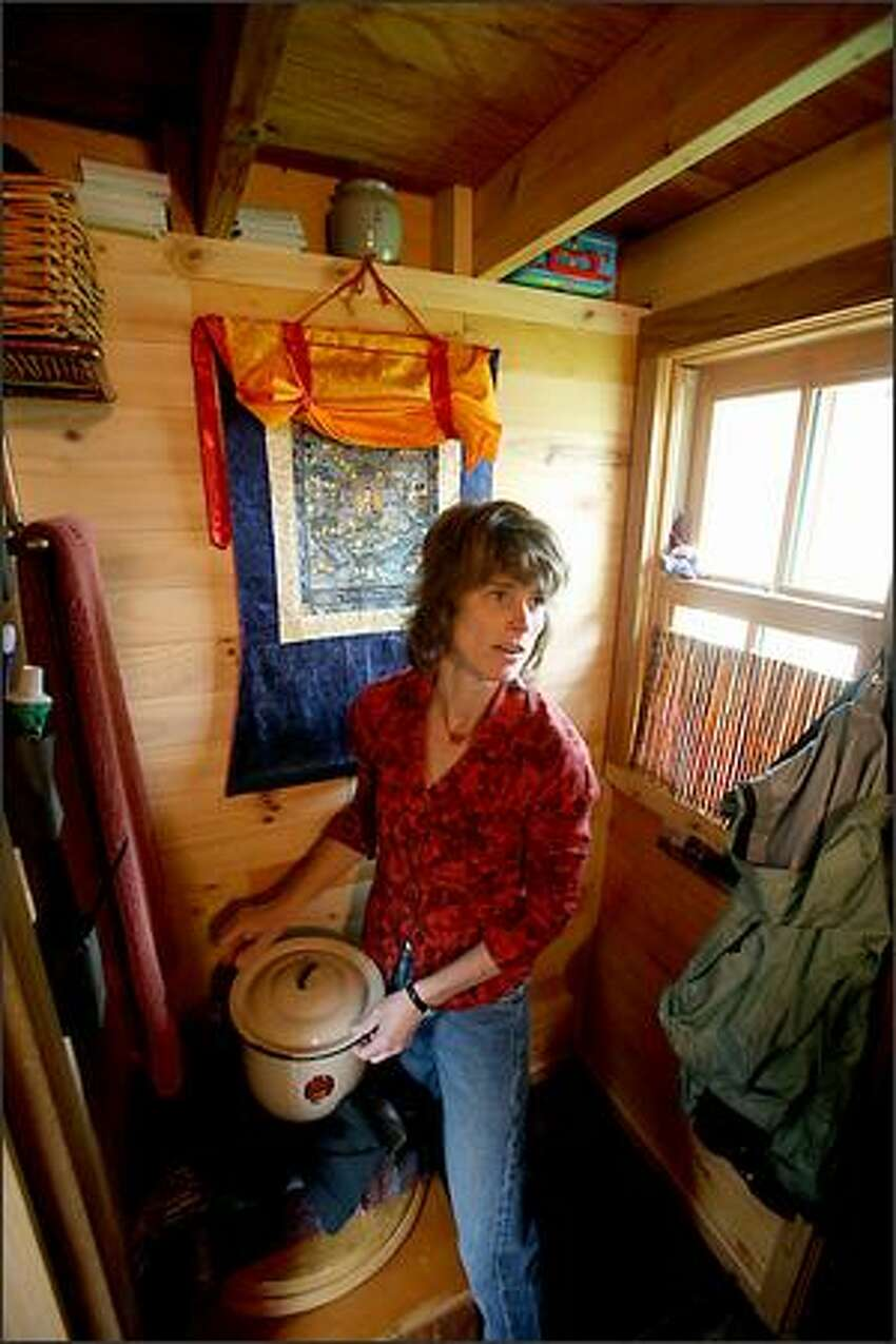 Dee Williams in the bathroom area of her 84-square-foot wooden Tumbleweed house on wheels.