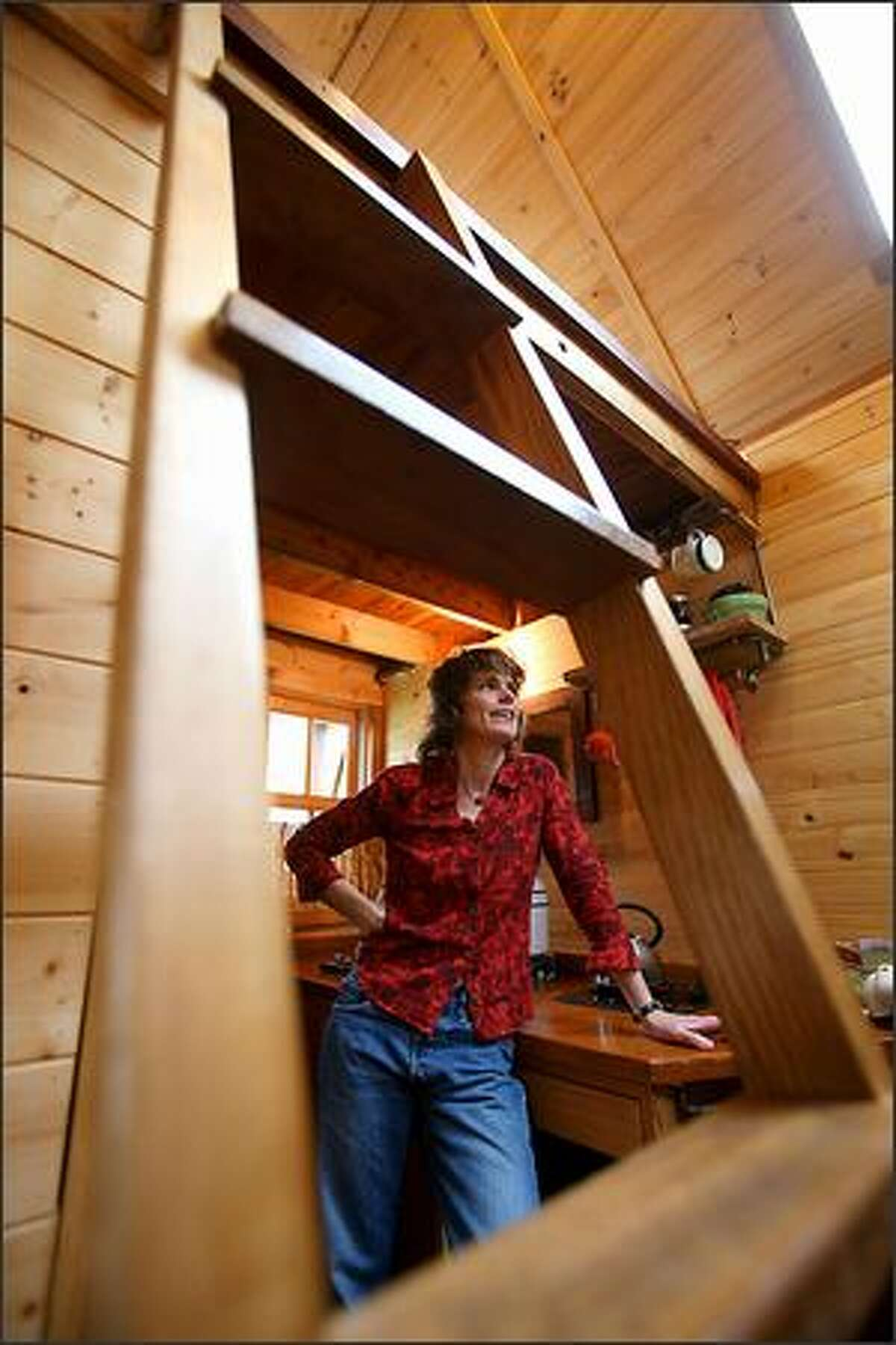Dee Williams, photographed through the steps leading up to her sleeping loft, lives in an 84-square-foot wooden Tumbleweed house on wheels in a neighbor's backyard.
