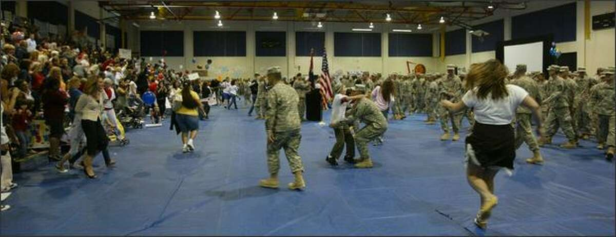 Family members and soldiers breakout of formation rush to each other after a 15-month deployment to Iraq.