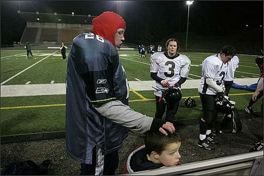 During practice, linewoman Heidi Corey shares a moment with her girlfriend's son, the team's biggest fan, Wee Man (Brandon Powell).