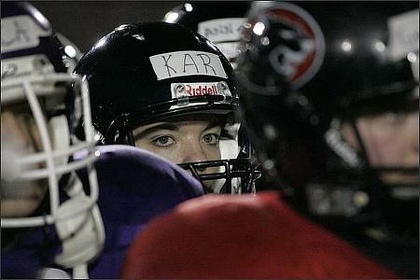 Wide receiver Karlene Clapp listens to coach Mike Talley at the beginning of practice at Kent Meridian High School.