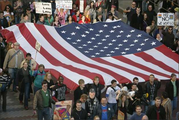 Protestors march into downtown Seattle carrying a huge American flag. Photo: Paul Joseph Brown/Seattle Post-Intelligencer