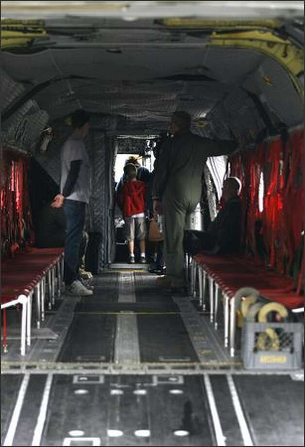 Interested folks check out the cockpit of the CH-47 Chinook helicopter at the American Heroes Air Show, Saturday, June 14, 2008. This is the fourth year the show has been in Seattle, with about 15 aircraft on display to the public. Photo: Kristine Paulsen, Seattle Post-Intelligencer