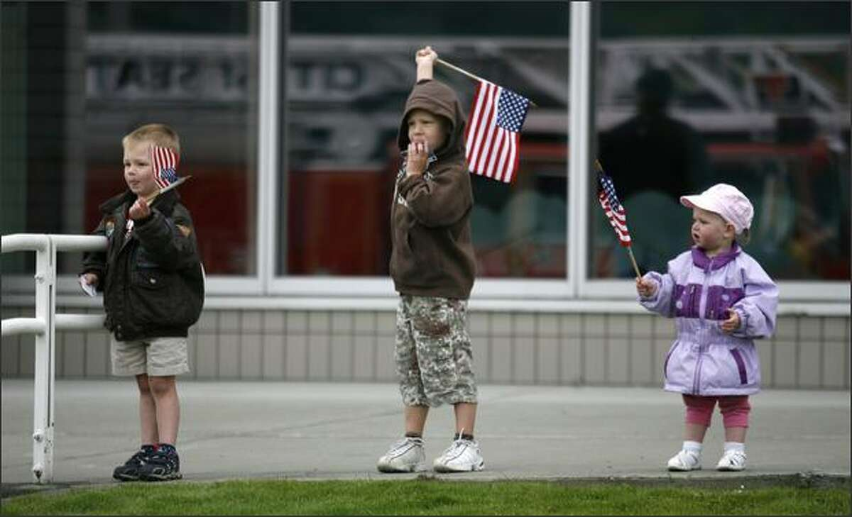 Noah, Isaiah and Hannah Dykstra wave their flags as a helicopter flies in to the American Heroes Air Show, Saturday, June 14, 2008. This is the fourth year the show has been in Seattle, with about 15 aircraft on display to the public.