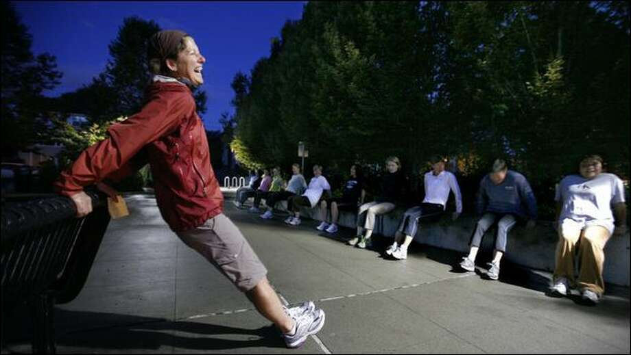 Christi Masi, a fitness trainer with The Healthy Goddess, leads a workout of mothers who meet twice a week before dawn at the Madrona Playground in Seattle. In addition to shoulder-blade push-ups, the group runs stairs and hauls sandbags. Photo: Paul Joseph Brown/Seattle Post-Intelligencer