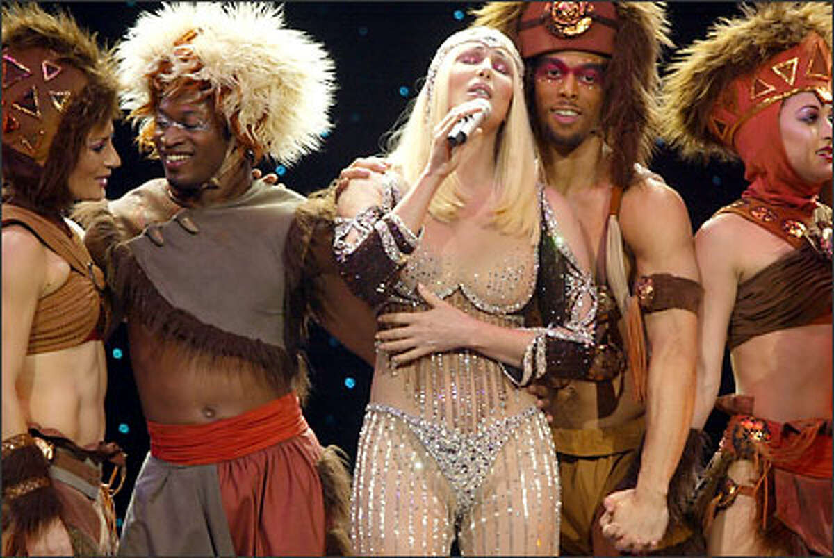 Surrounded by some of her dancers, Cher performs her ornate-costume concert in her long-running