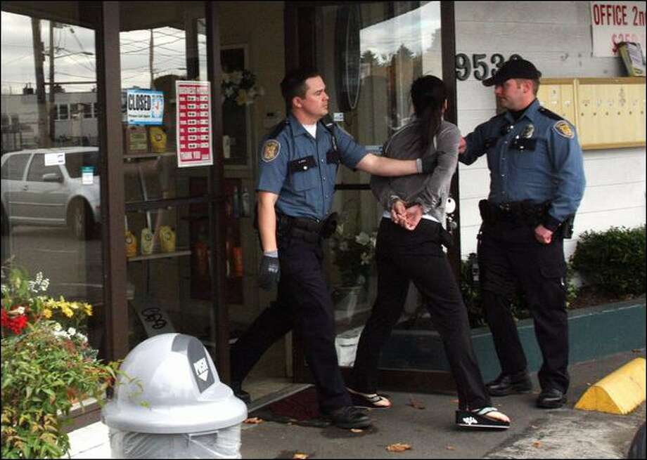Seattle police officers lead a woman out of a business on Aurora Avenue on Tuesday that authorities say was a front for prostitution. Two people were indicted. Photo: Karen Ducey/Seattle Post-Intelligencer