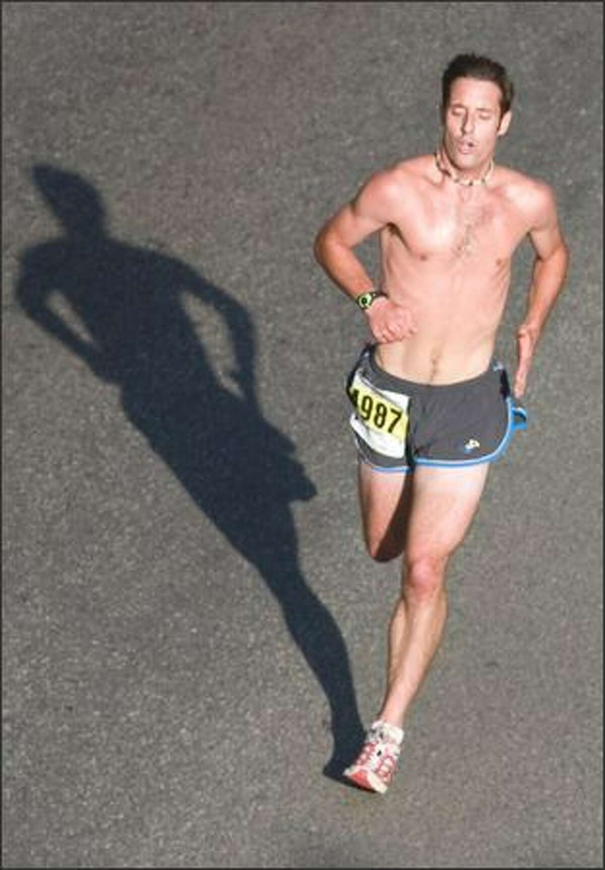 A runner casts his shadow on 520 during the Virginia Mason Team Medicine Seafair Marathon.