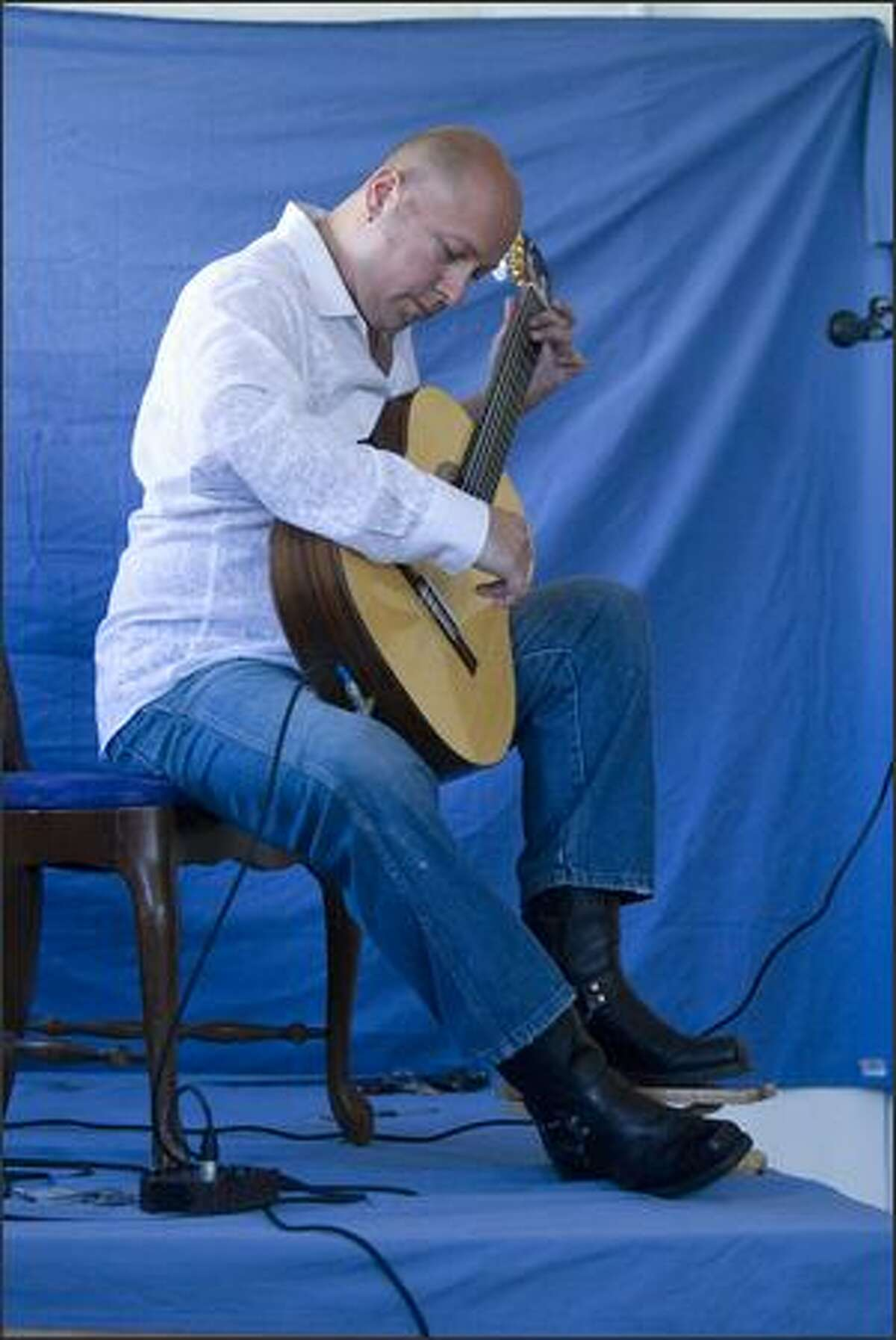 Andre Feriante's guitar style blends classical and Spanish styles for a small group at Artopia in Georgetown's historic business district Saturday.