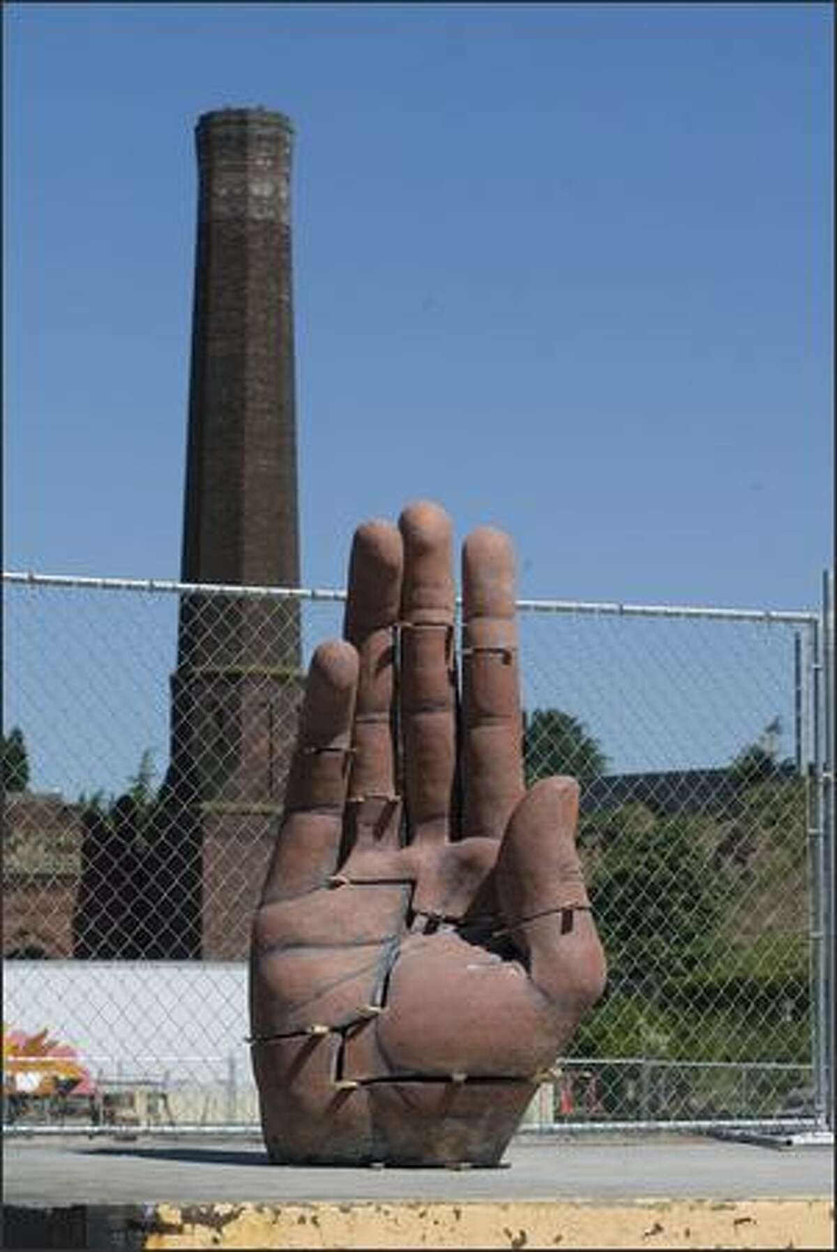 A giant hand near the site of the old ice house seems to be signaling to stop the destruction of the old buildings in Georgetown.