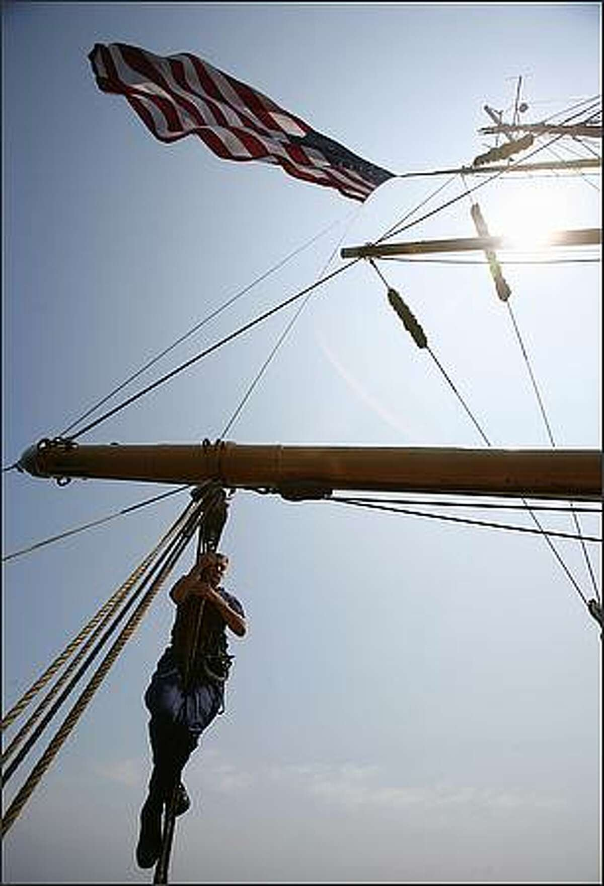 Member of the Coast Guard Sharon Mezulis climbs after hoisting the U.S. flag aboard the U.S. Coast Guard Barque Eagle.
