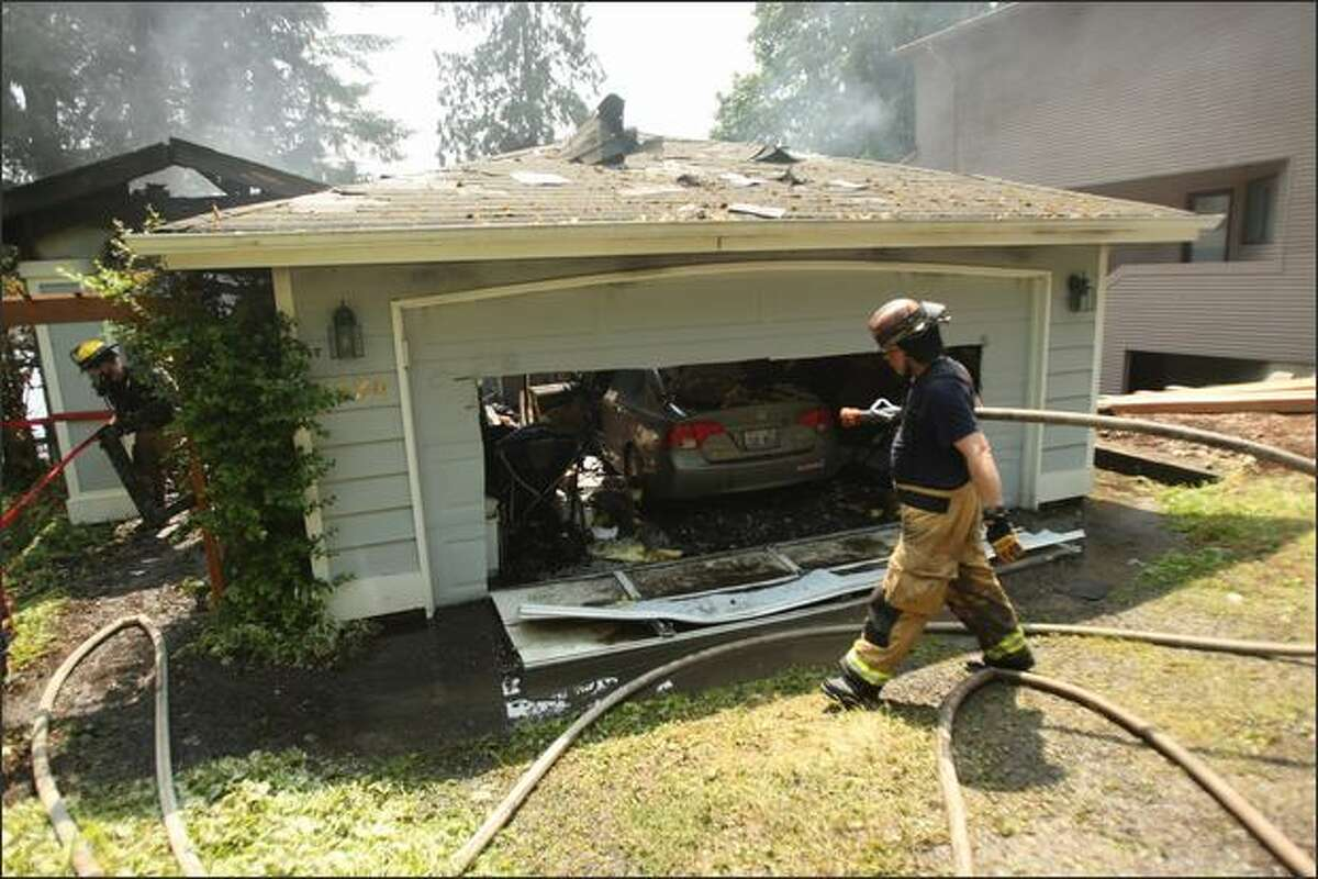 Redmond firefighters work the scene of a fire that burned through the Ames Lake house of Darcy Burner near Carnation on Tuesday.