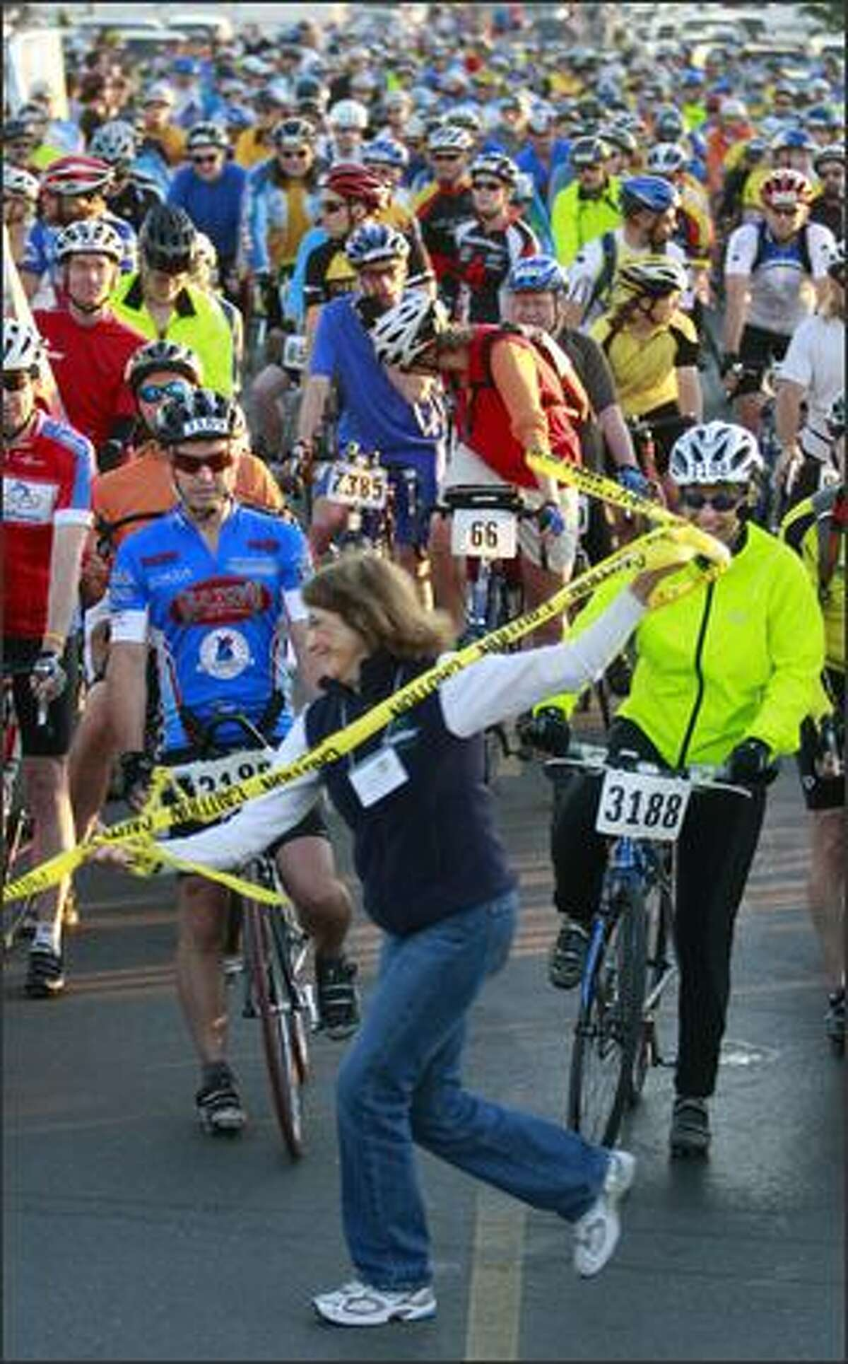 Diane English of the Cascade Bicycle Club removes the restraining tape, allowing bicyclists to begin the ride.